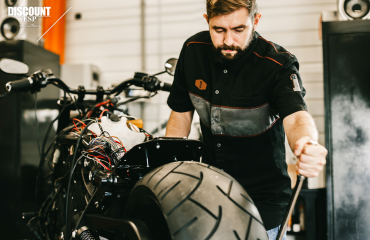 Repair man fixes motorcycle for customer with extended service plan